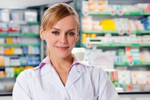 Young pharmacist in work, smiling. We can see the pharmacy store shelves behind her