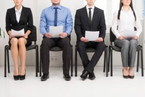Illustration of a tough competition in a pharmacy interview. We can see four job applicants sitting on chairs, looking nervous. They hold their resumes in their hands. Two men sit in the middle, and one woman sits on each side.