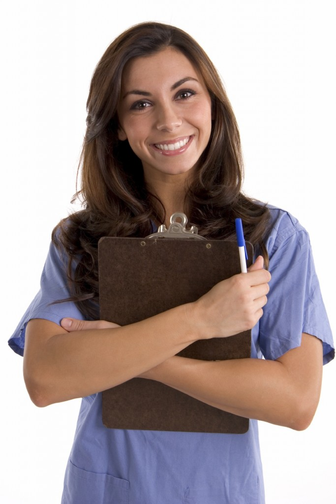 A very happy pharmacist, a young beautiful woman, she is holding a pen in her hand, and she smiles. She wears blue shirt