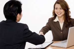 A woman shake hands with a job appliant. Both are in a good mood. We can see a silver laptop on the table.